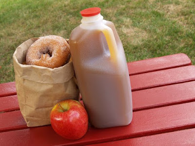 a bottle of apple cider and a bag of sugar donuts