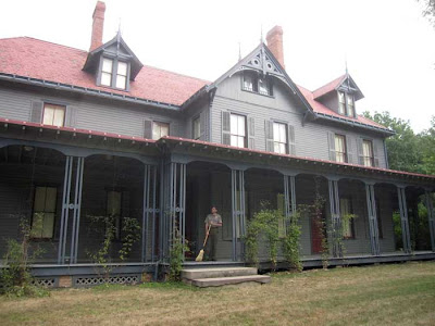 Gray Queen Anne-style house with red roof, porch all along the front