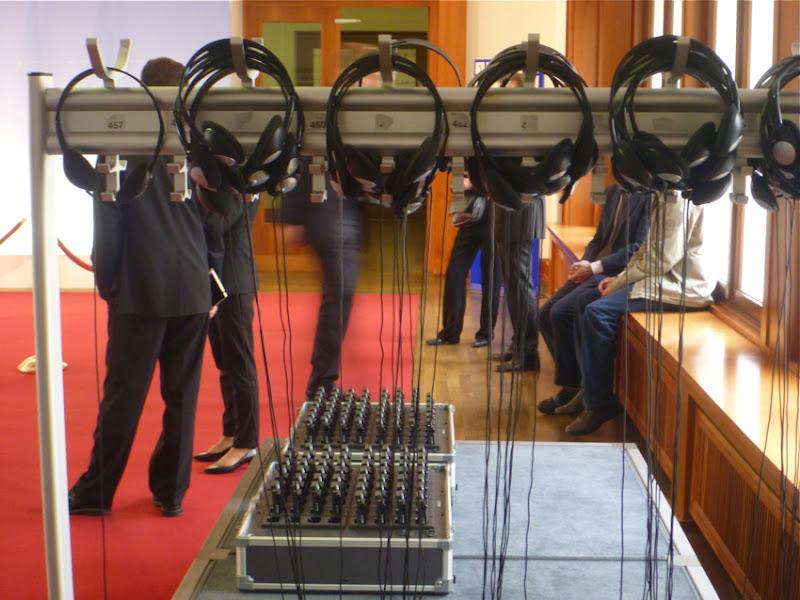 Dolmetschtechnik (Kopfhörer und Empfänger) vor einer Pressekonferenz, dahinter Anzugträgerinnen und -träger