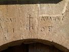 Detall de la inscripció a les dovelles superiors del portal del Mas de les Claperoses