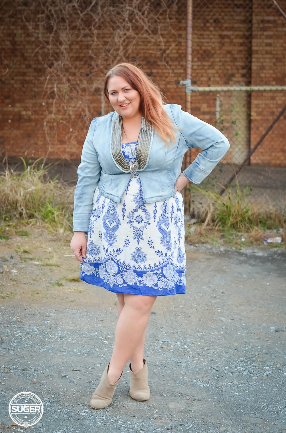 Melissa from Suger Coat It blog wearing denim jacket over blue and white dress
