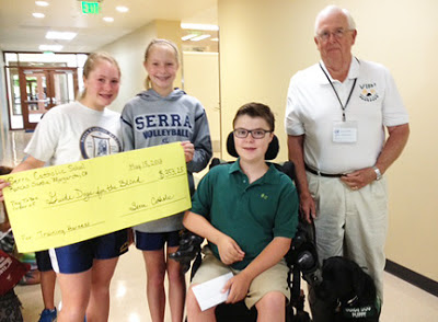 Serra Catholic School students hold up a check for funds they raised from their recycle program to benefit GDB.