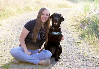 Kylie sits on a dirt road next to a smiling black Lab guide dog puppy.