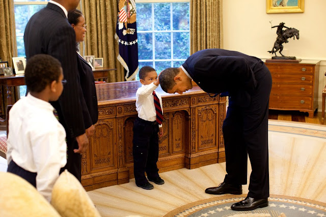President Obama bends over so the son of a White House staffer can pat his head. He wanted to see if the President's haircut felt like his.