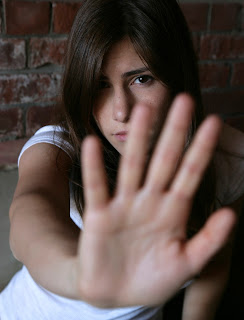 Concerned young woman holds hand to the camera to say stop.