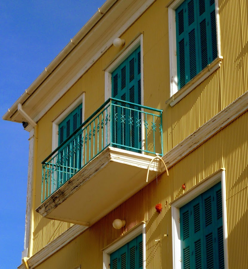 Architektur in Lefkas Stadt: Wellblech in Gelb und blaue Fensterläden