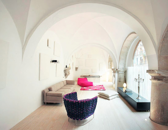 cloister in Barcelona turned into a modern living room with purple and pink accent chairs