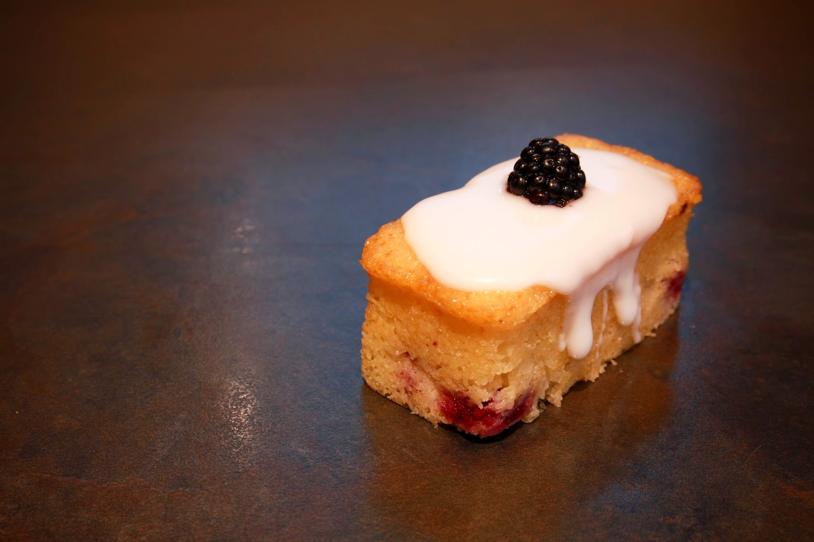 Blackberry and yoghurt mini loaf cake topped with lemon icing and a blackberry