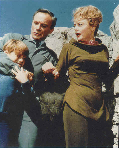 Dr. Smith holding Will tight while Maureen Robinson looks on in http://movieloversreviews.blogspot.com