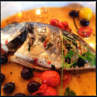 Whole roasted sea bream, garlic, Heritage tomatoes and olives