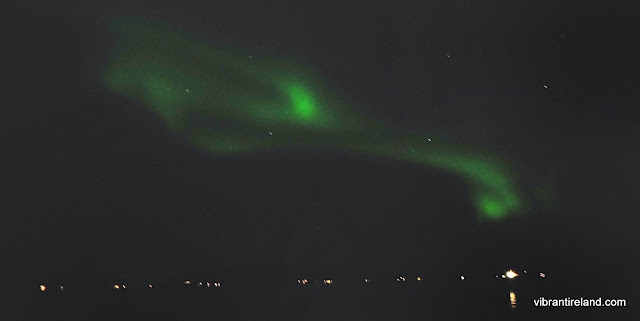 green swirls of aurora over the fjord norway