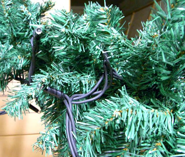 Lichterkette falsch auf künstliche grüne Weihnachtsgirlande gelegt, die einzelnen Lämpchen sieht man nicht mehr
