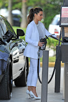 Kim Kardashian dressed in white at a gas station