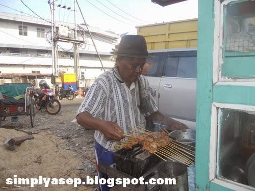 Penjual sedang memasak satenya