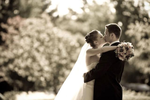 жених и невеста целуются рядом с машиной