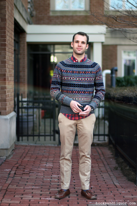 This male student wore a black grey and red fair isle patterned sweater over a red and blue plaid shirt and khaki pants, blue socks and brown leather moccasins.