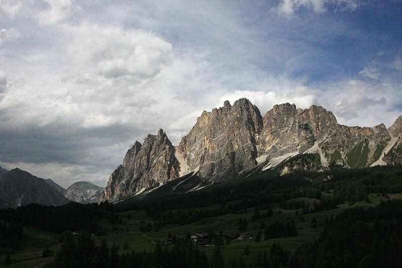Imagem com campos verdejantes em primeiro plano e montanhas bem iluminadas ao fundo. Céu luminoso mas com núvens