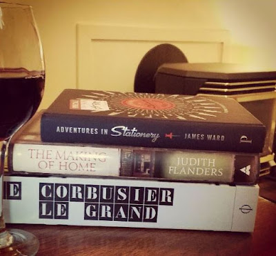 Three books in a pile next to a glass of red wine.
