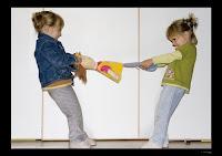 Niñas tirando de una muñeca en sentido opuesto