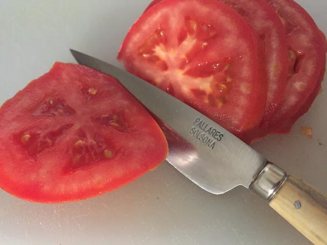 Ensalada de atún naturfresh con anchoas. Cortando tomate.