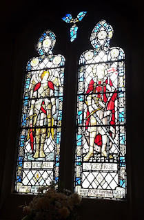 Two colourful stained glass windows depicting armoured men.