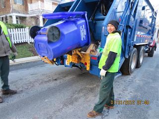 Recycling crew emptying a paper recycling cart into its truck