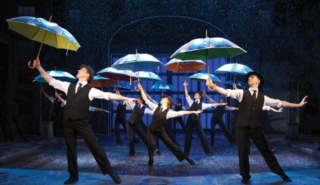 Singin in the rain cast with umbrellas during dance routine on the stage