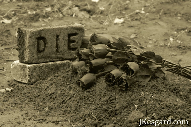 A gravesite with black roses and a headstone that says DIE