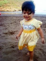 anak kecil cantik bermain pasir di pantai