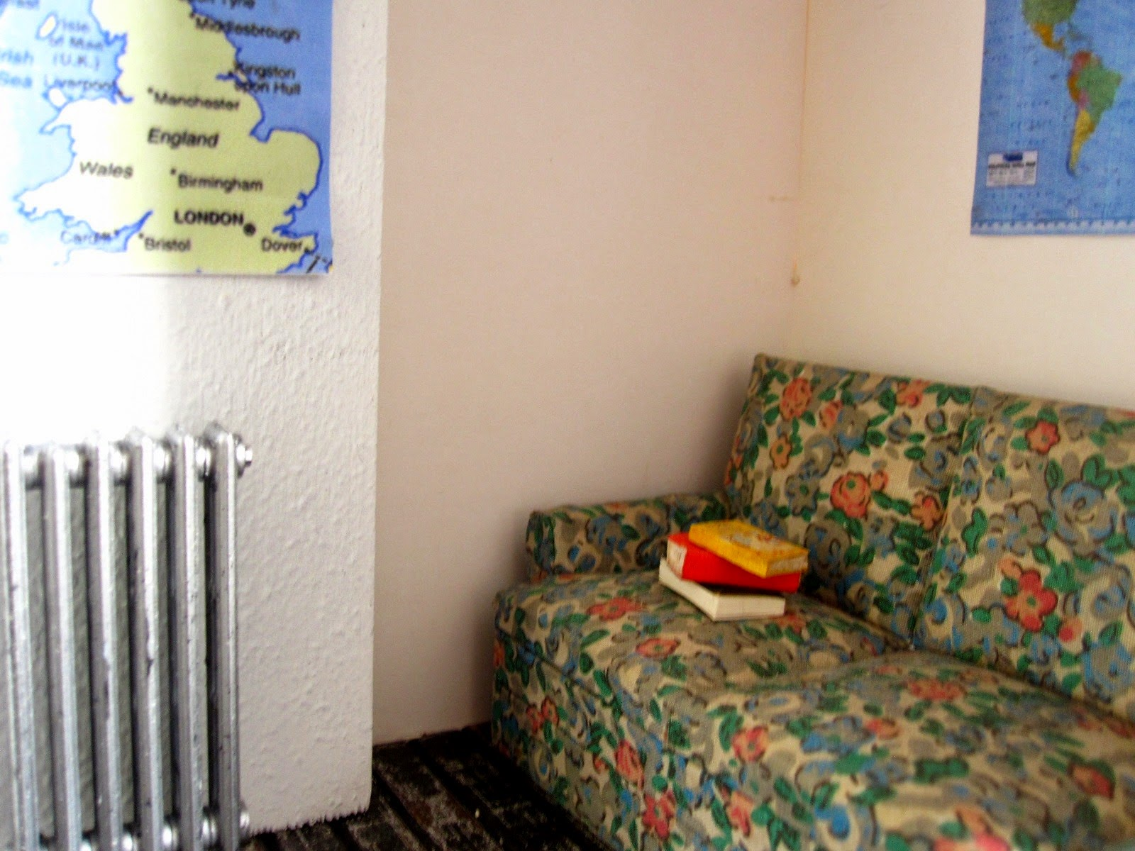 Sofa in the corner of a modern dolls' house miniature pop-up Little Library, On the wall above it are some vintage maps.