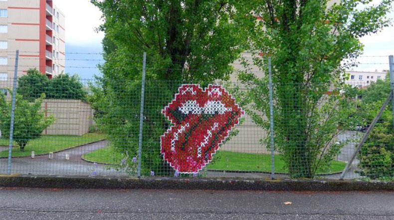 Artista crea colorido arte en punto cruz sobre cercas de ciudad
