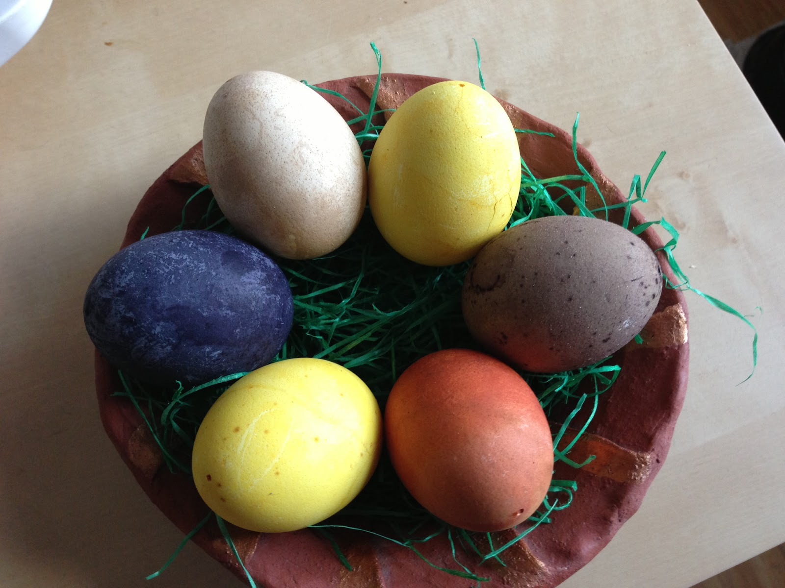 Eggs dyeing in natural color . Clockwise from the top right we have turmeric (yellow), red wine (purple-ish), onion skin (brick red), another turmeric, blue berry (dark blue), and last and kind of least: paprika powder.