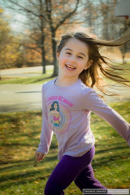 A young girl beams as she runs past the camera, her hair flying.