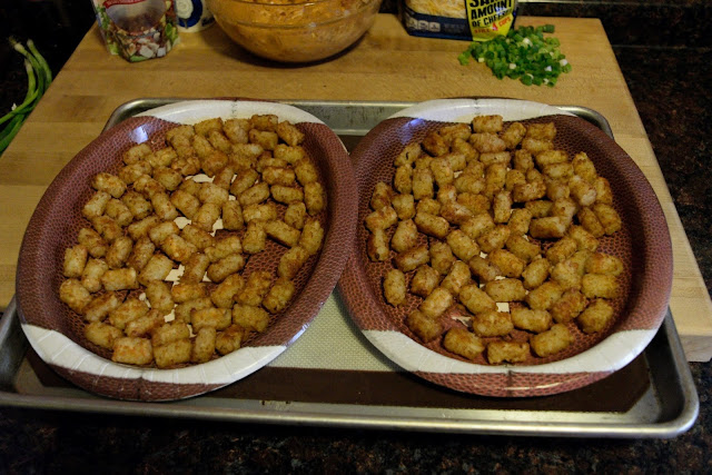 A picture of the two football plates, on a baking sheet, filled with the cooked tater tots.