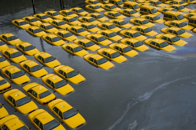 In this Oct. 30, 2012 file photo, a parking lot full of yellow cabs in Hoboken, N.J. is flooded as a result of Superstorm Sandy. (Credit: AP Photo/Charles Sykes)  Click to Enlarge.