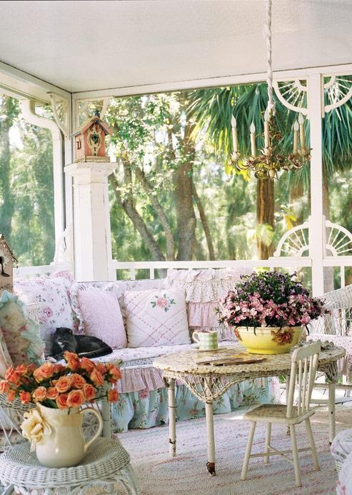 This screened in front porch decor is light and springy - love the fabric patterns on the couch and how they match the spring flower arrangements
