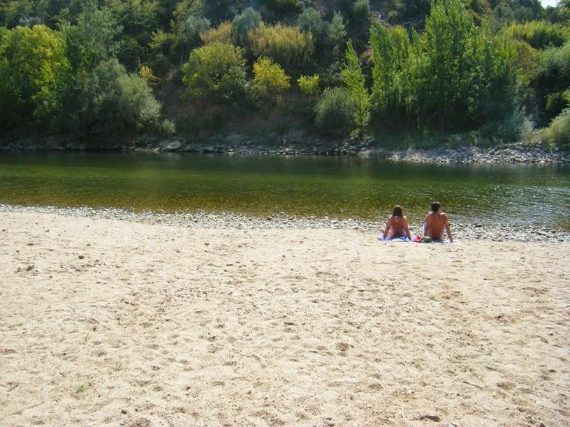Pessoas a apanhar sol na margem do Zêzere