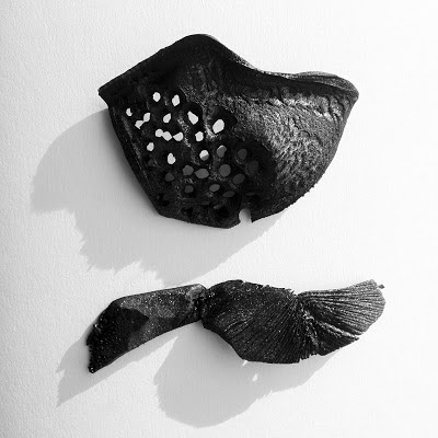 Two black sculptures made out of polysytrene.