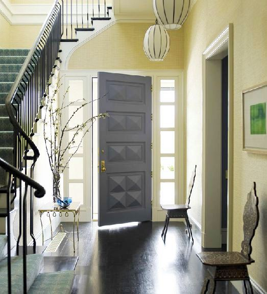 Foyer in Katie Ridder's home with pendant light, sea grass wallpaper, dark wood floor, Moroccan chairs, staircase, and a grey moulded door