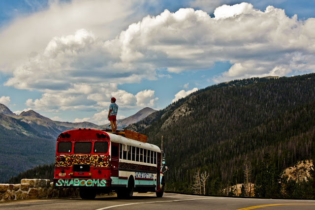 A guy on top of the Shabooms bus getting a better view in Rocky Mountain National Park.