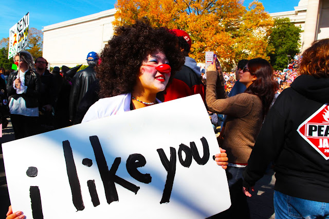 "A girl wearing an afro wig and a clown nose holding a sign that says 'i like you""."
