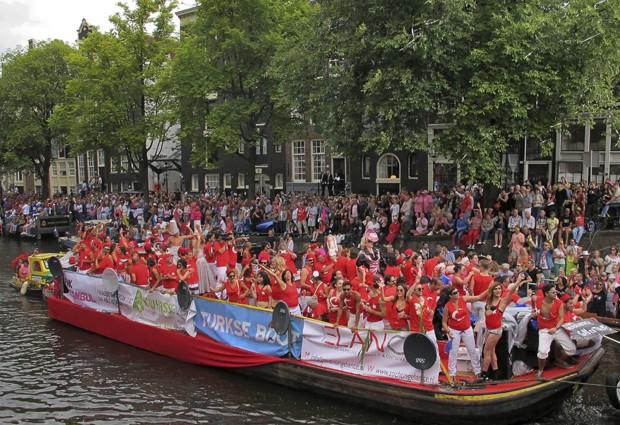 Turcos dançam em um barco durante a Parada do Canal, no Prinsengracht, em Amsterdã. (Foto: Margriet Faber/AP)