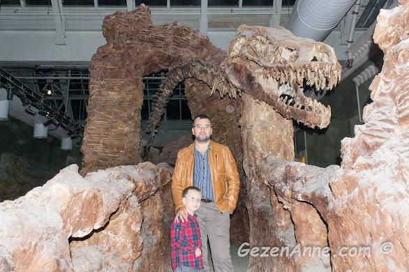 fossiller arasında fırlamış bir dinozor kafası önünde oğlum ve babası poz verirken, Jurassic Land İstanbul