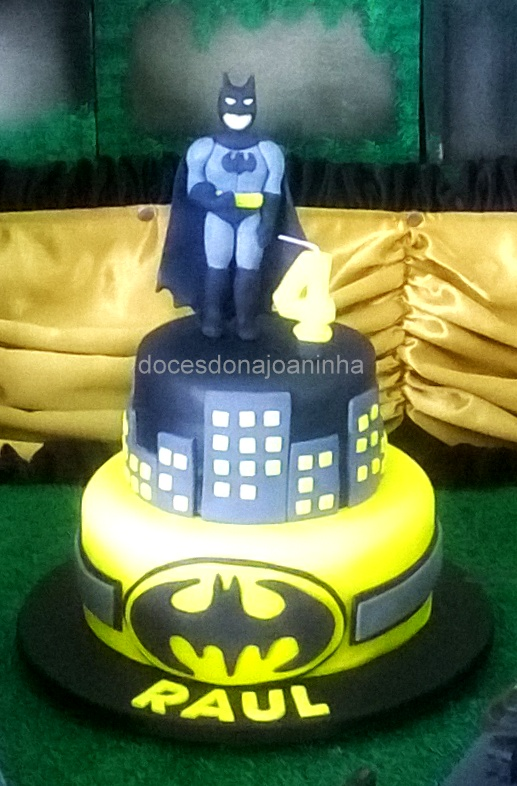 Bolo decorado do Batman em amarelo e preto com predios e logo do morcego.