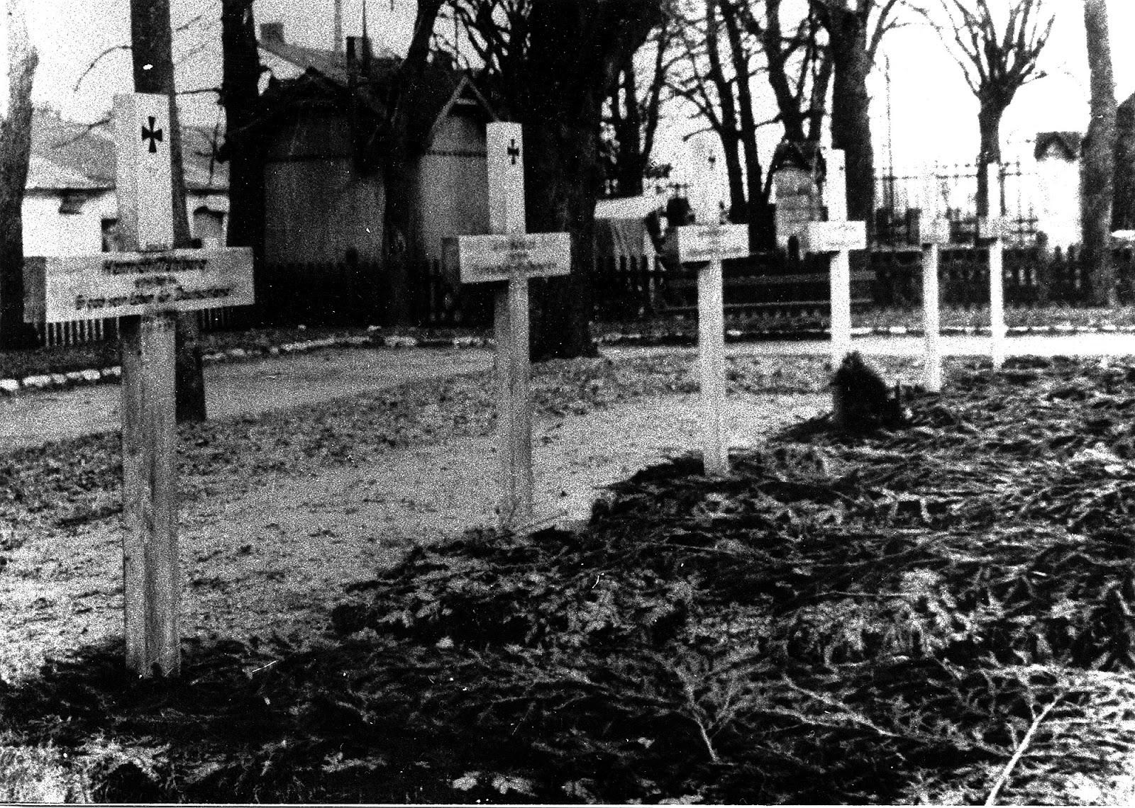 Widok na Ehrenfriedhof Konskie. Na pierwszym planie groby żołnierzy ekshumowanych wiosną 1940 roku w Kazanowie i przeniesionych do Końskich. Zdjęcie wykonane zapewne jesienią 1940 roku. W głębi ogrodzenie kościoła p.w. św. Mikołaja. Skan fotografii udostępnił Ryszard Cichoński.