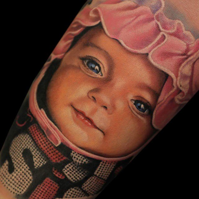 very realistic baby face arm tattoo design, done by a russian tattoo