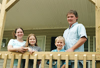 Gibson husband, wife and two children in their new home