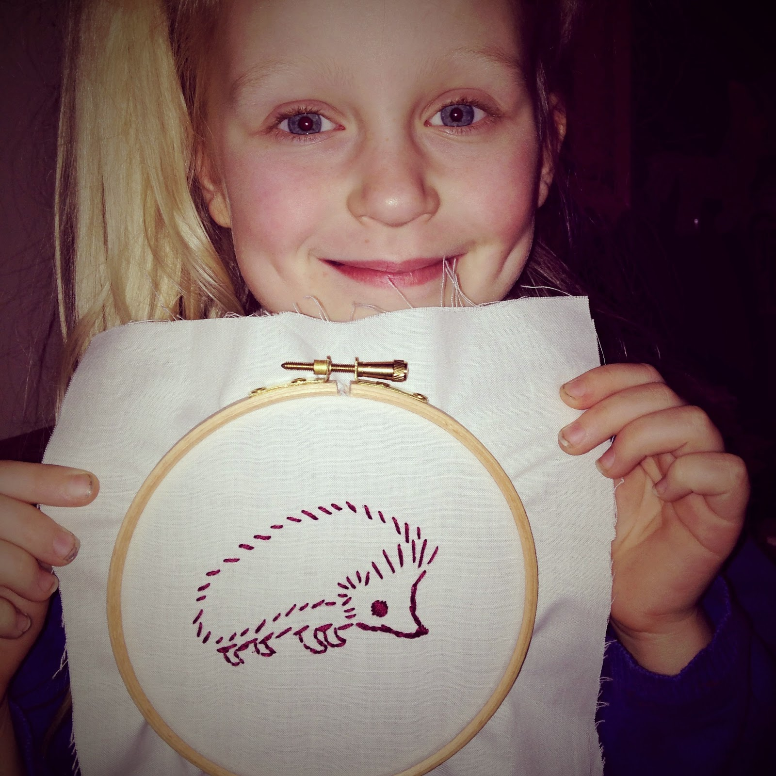 girl holding embroidery of hedgehog