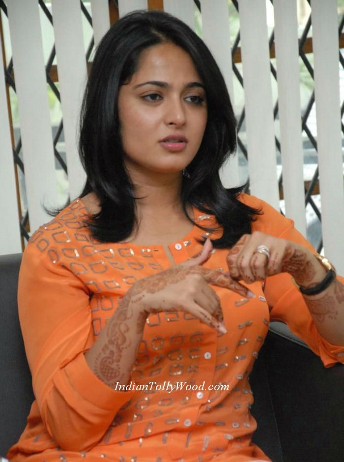 .actress Anushka in orange top white pant photos.Anushka in orange