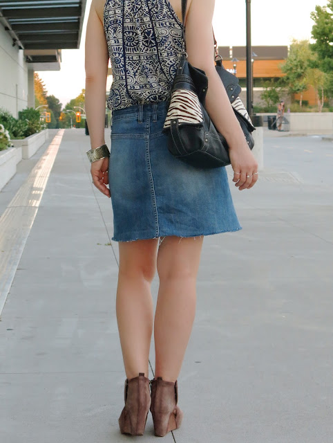 peasant-style patterned camisole with a denim skirt, open-toe booties, and a zebra-stripe-embellished bag